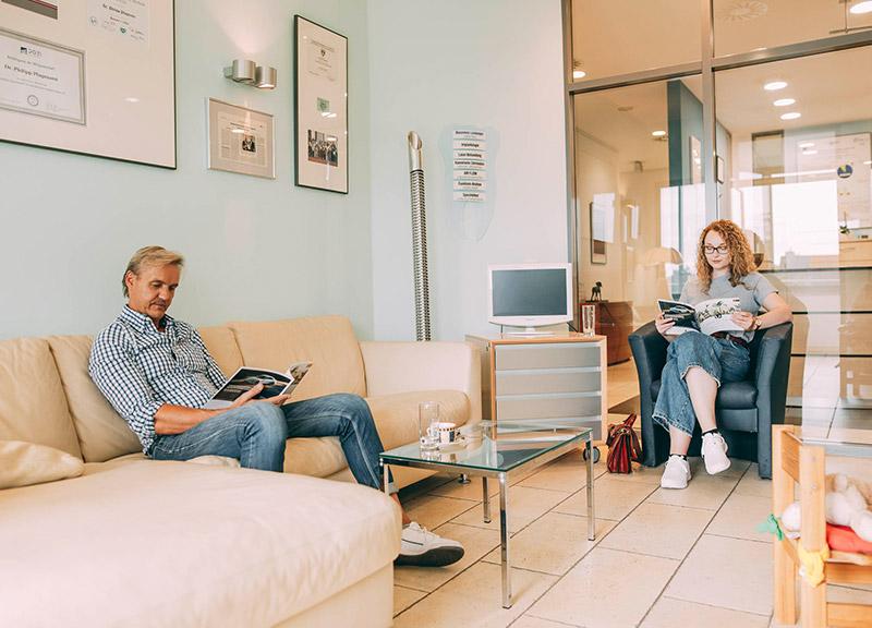 Patienten warten im gemütlichen Wartezimmer in der Zahnarztpraxis Plugmann