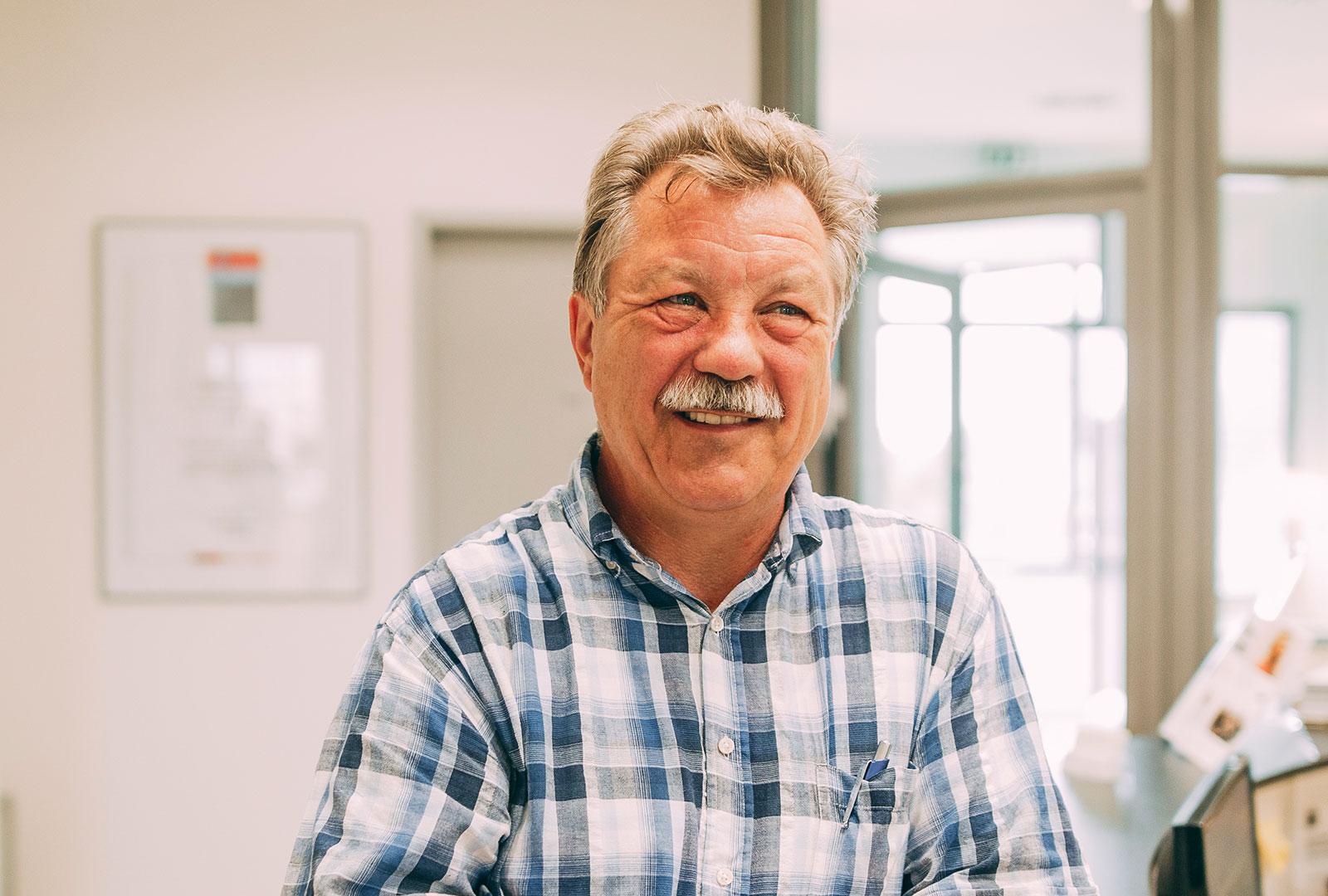 Mann freut sich über sicheren Zahnersatz auf Zahnimplantaten in Leverkusen